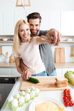 Portrait of happy young couple cooking together in the kitchen Stock Images