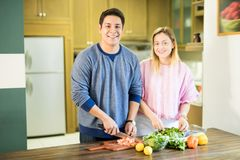 Happy young couple making vegetable salad royalty free stock photography