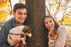 Portrait of happy young couple with dogs outdoors in park Royalty Free Stock Images