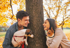 Portrait of happy young couple with dogs outdoors in park Royalty Free Stock Photography
