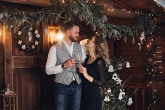 Beautiful couple with champagne under Christmas wreath. royalty free stock photos