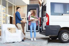 Happy Young Couple Loading Moving Van. Portrait of happy  young couple embracing and smiling while loading cardboard boxes to moving van outdoors Royalty Free Stock Images