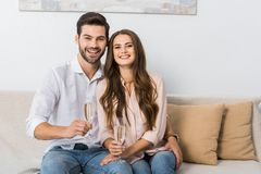 portrait of happy young couple with glasses of champagne resting on sofa royalty free stock image