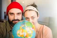 Portrait of Happy young couple with globe choosing place for summer journey. Family travel concept. Portrait of Happy young couple with globe choosing place for royalty free stock photo