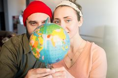 Portrait of Happy young couple with globe choosing place for summer journey. Family travel concept. Portrait of Happy young couple with globe choosing place for stock photography
