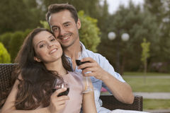 Portrait of happy young couple having red wine together in park Stock Photos