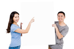 Portrait of happy young couple holding blank billboard. Against white background Royalty Free Stock Photos