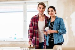 Portrait of a happy young couple holding tools for home remodeling. Portrait of a happy young couple wearing casual clothes while holding tools for home royalty free stock images