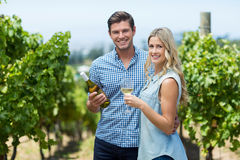Portrait of happy young couple holding wine bottle and glass Stock Image