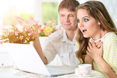 Young couple with laptop. Portrait of happy young couple with laptop at home Royalty Free Stock Photography