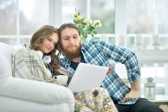 Happy young couple with laptop. Portrait of happy young couple with laptop at home Royalty Free Stock Photo