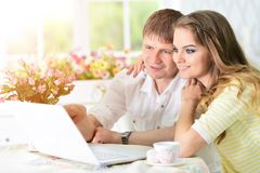 Young couple with laptop. Portrait of happy young couple with laptop at home Royalty Free Stock Image