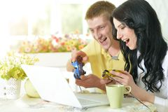 Young couple with laptop. Portrait of happy young couple with laptop playing game at home Stock Photo