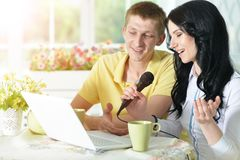 Young couple with laptop. Portrait of happy young couple with laptop  singing karaoke at home Royalty Free Stock Photos