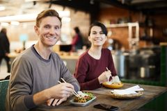 Clients in Chinese Food Restaurant. Portrait of happy young couple looking at camera while enjoying Asian food in restaurant, copy space stock image
