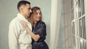 Portrait of happy young couple in love in bathrobes are looking out the window stock images