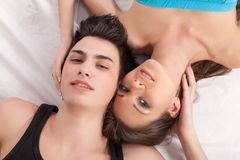 Portrait of happy young couple lying in bed and smiling Royalty Free Stock Image