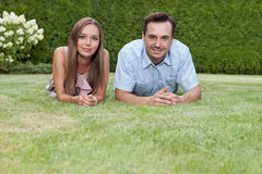Portrait of happy young couple lying on grass in park Royalty Free Stock Photo