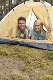 Portrait of happy young couple lying in tent Royalty Free Stock Images