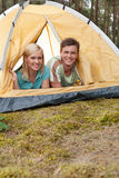 Portrait of happy young couple lying in tent stock image