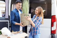 Happy Young Couple Moving In. Portrait of happy young couple moving in new home, holding house plant and smiling outdoors royalty free stock photos