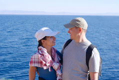 Portrait of happy young couple outside on coast over blue sea Royalty Free Stock Photo