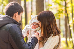 Portrait of a happy young couple playing with their cute newborn baby Royalty Free Stock Photos