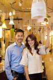 Portrait of a happy young couple with price tag in lights store Stock Photo