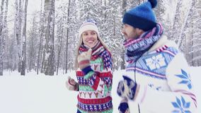Portrait of happy young couple running in the forest. Portrait of happy young couple in bright winter clothes running in the forest. Slow motion stock video