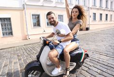 Cheerful young couple riding a scooter and having fun Royalty Free Stock Photo