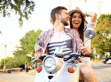 Portrait of happy young couple on scooter enjoying road trip. Couple in love riding a motorbike , Handsome guy and young women travel . Young riders enjoying stock photo