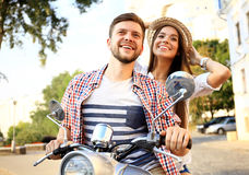 Portrait of happy young couple on scooter enjoying road trip Royalty Free Stock Image