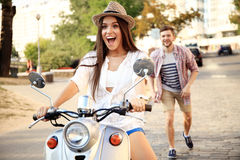 Portrait of happy young couple on scooter enjoying road trip Stock Photos