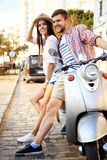 Portrait of happy young couple on scooter enjoying road trip Stock Photography