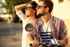 Portrait of happy young couple on scooter enjoying road trip Royalty Free Stock Photo