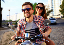 Portrait of happy young couple on scooter enjoying road trip Royalty Free Stock Images
