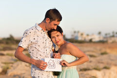 Portrait of happy young couple showing house drawn on paper outdoors Royalty Free Stock Photos