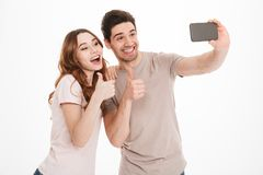 Portrait of a happy young couple showing thumbs up. While taking a selfie together isolated over white background Royalty Free Stock Photography