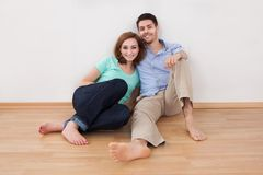 Portrait of happy young couple sitting on floor Royalty Free Stock Photo