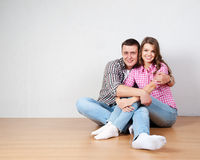Portrait Of Happy Young Couple Sitting On Floor Looking Up Ready. For your text or product Stock Images