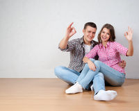 Portrait Of Happy Young Couple Sitting On Floor Looking Up Ready Royalty Free Stock Photo