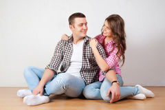 Portrait Of Happy Young Couple Sitting On Floor Looking Up Ready for your text or product Royalty Free Stock Photography