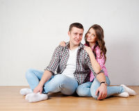 Portrait Of Happy Young Couple Sitting On Floor Looking Up Ready for your text or product Royalty Free Stock Images