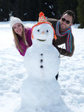 Portrait of happy young couple with snowman Stock Photo