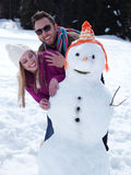 Portrait of happy young couple with snowman Royalty Free Stock Images