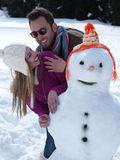 Portrait of happy young couple with snowman Stock Photos