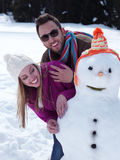 Portrait of happy young couple with snowman Royalty Free Stock Photography