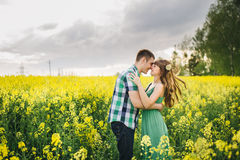 Portrait of happy and young couple standing among flowers in field and embracing. Side view of brunette wife and handsome husband Stock Image