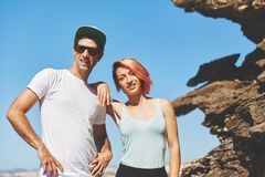Happy young couple standing together by the rock Stock Image