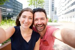 Portrait of happy young couple taking selfie outside in city Stock Photo